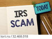 Купить «Text sign showing Irs Scam. Conceptual photo Warning Scam Fraud Tax Pishing Spam Money Revenue Alert Scheme written Notebook Book the wooden background Today Pencil next to it.», фото № 32468018, снято 13 декабря 2019 г. (c) easy Fotostock / Фотобанк Лори