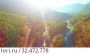Купить «Mid air flight over fresh mountain river and meadow at sunny summer morning. Rural dirt road below.», видеоролик № 32472778, снято 29 мая 2017 г. (c) Александр Маркин / Фотобанк Лори