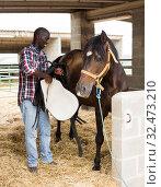 Купить «Young man farmer removes saddle from horse at stable at farm», фото № 32473210, снято 6 августа 2019 г. (c) Яков Филимонов / Фотобанк Лори
