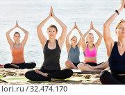 Купить «Girls practicing yoga in lotus position on beach», фото № 32474170, снято 22 мая 2017 г. (c) Яков Филимонов / Фотобанк Лори
