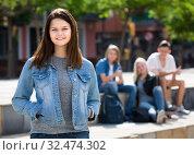 Купить «Portrait of teenager girl standing aside from friends outdoors», фото № 32474302, снято 7 декабря 2019 г. (c) Яков Филимонов / Фотобанк Лори