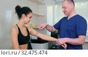 Купить «Chiropractic treatment - the doctor specialist testing out the reaction on Wartenberg Wheel on young woman's body», видеоролик № 32475474, снято 20 февраля 2020 г. (c) Константин Шишкин / Фотобанк Лори