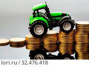 Bauern in der Landwirtschaft haben mit steigenden Kosten zu rechnen. Höhere Preise bei Futter, Dünger und Pflanzen. Traktor mit Münzen. Стоковое фото, фотограф Zoonar.com/Erwin Wodicka - wodicka@aon.at / age Fotostock / Фотобанк Лори