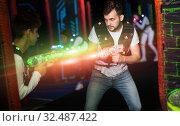 Купить «Excited guy laser tag player in bright beams», фото № 32487422, снято 25 апреля 2018 г. (c) Яков Филимонов / Фотобанк Лори