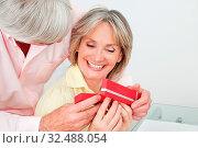 Lachende Seniorin bekommt von ihrem Mann ein Geschenk überreicht. Стоковое фото, фотограф Zoonar.com/Robert Kneschke / age Fotostock / Фотобанк Лори