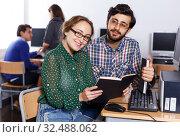 Купить «students reading textbook together while studying», фото № 32488062, снято 14 ноября 2018 г. (c) Яков Филимонов / Фотобанк Лори