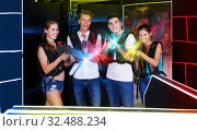 Купить «Young people posing with laser pistols», фото № 32488234, снято 27 августа 2018 г. (c) Яков Филимонов / Фотобанк Лори