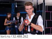 Happy young man with laser pistol and playing laser tag with his friends. Стоковое фото, фотограф Яков Филимонов / Фотобанк Лори