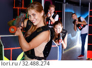 Portrait of exciting girl with laser pistol playing laser tag in dark room. Стоковое фото, фотограф Яков Филимонов / Фотобанк Лори