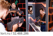 Купить «Laser tag players guys and girls playing in teams in dark laser tag room», фото № 32488286, снято 27 августа 2018 г. (c) Яков Филимонов / Фотобанк Лори