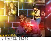 Купить «African man playing laser tag with friends», фото № 32488570, снято 23 января 2019 г. (c) Яков Филимонов / Фотобанк Лори