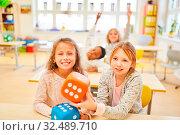 Zwei Mädchen in der Vorschule lernen rechnen bei einem Lernspiel mit Würfel. Стоковое фото, фотограф Zoonar.com/Robert Kneschke / age Fotostock / Фотобанк Лори