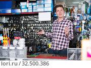 Купить «worker in hardware store trading goods and keys in uniform», фото № 32500386, снято 4 мая 2017 г. (c) Яков Филимонов / Фотобанк Лори