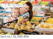 Купить «Portrait of happy woman and her little son choosing pears and apples at shop», фото № 32500454, снято 20 апреля 2019 г. (c) Яков Филимонов / Фотобанк Лори