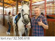 Купить «Mature positive man farmer standing with white horse at stabling», фото № 32500618, снято 4 июля 2018 г. (c) Яков Филимонов / Фотобанк Лори