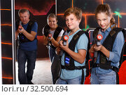 Teenage boy and sister aiming laser guns during laser tag game with parents. Стоковое фото, фотограф Яков Филимонов / Фотобанк Лори