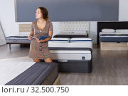 Купить «woman reading brochure while choosing new mattress», фото № 32500750, снято 22 октября 2018 г. (c) Яков Филимонов / Фотобанк Лори