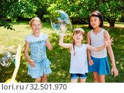 Kinder spielen zusammen im Park im Sommer und fangen Seifenblasen. Стоковое фото, фотограф Zoonar.com/Robert Kneschke / age Fotostock / Фотобанк Лори