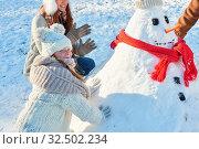 Mädchen baut mit seinen Eltern einen Schneemann im Winter im Garten. Стоковое фото, фотограф Zoonar.com/Robert Kneschke / age Fotostock / Фотобанк Лори