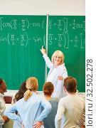 Купить «Mathematik Dozentin zeigt Studenten die Lösung einer Formel», фото № 32502278, снято 5 августа 2020 г. (c) age Fotostock / Фотобанк Лори