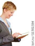 Junge lachende Frau tippt mit Zeigefinger auf einen Tablet PC. Стоковое фото, фотограф Zoonar.com/Robert Kneschke / age Fotostock / Фотобанк Лори