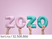 Купить «Hands holding numbers numbers 2020 made of pink and mint foil balloons on pink background», фото № 32508866, снято 27 ноября 2019 г. (c) Kira_Yan / Фотобанк Лори