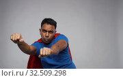 Купить «indian man in superhero cape flying over grey», видеоролик № 32509298, снято 26 ноября 2019 г. (c) Syda Productions / Фотобанк Лори