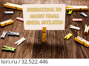 Купить «Text sign showing International Day Against Female Genital Mutilation. Conceptual photo awareness day February Clothespin holding white paper note several clothespins wooden floor», фото № 32522446, снято 31 мая 2020 г. (c) easy Fotostock / Фотобанк Лори