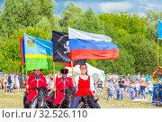 Купить «Russia, Samara, July 2019: Solemn entry of a group of horse racing with flags in the meadow of the festival.», фото № 32526110, снято 28 июля 2019 г. (c) Акиньшин Владимир / Фотобанк Лори