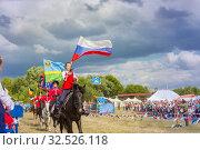 Купить «Russia, Samara, July 2019: Solemn entry of a group of horse racing with flags in the meadow of the festival.», фото № 32526118, снято 28 июля 2019 г. (c) Акиньшин Владимир / Фотобанк Лори