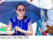 Купить «Russia, Samara, July 2019: Ethnic festival. Kazakh girl in national dress under an umbrella.», фото № 32526378, снято 28 июля 2019 г. (c) Акиньшин Владимир / Фотобанк Лори