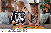 kids in halloween costumes doing crafts at home. Стоковое видео, видеограф Syda Productions / Фотобанк Лори