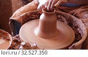 Купить «Closeup of male hands sculpting ceramics on potters wheel in pottery workshop», видеоролик № 32527350, снято 5 апреля 2020 г. (c) Яков Филимонов / Фотобанк Лори