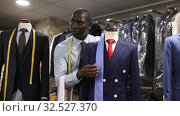 Купить «Afro-american man seller is showing jacket and tie in shop», видеоролик № 32527370, снято 2 июля 2019 г. (c) Яков Филимонов / Фотобанк Лори