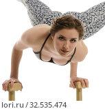 Купить «Acrobatics. Girl poses while doing handstand», фото № 32535474, снято 13 мая 2016 г. (c) Гурьянов Андрей / Фотобанк Лори