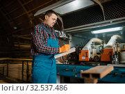 Carpenter in uniform holds notebook, lumber. Стоковое фото, фотограф Tryapitsyn Sergiy / Фотобанк Лори