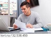 Купить «Smiling male with laptop analyzing domestic budget», фото № 32538450, снято 27 февраля 2020 г. (c) Яков Филимонов / Фотобанк Лори