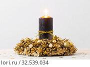 Купить «Christmas golden wreath with black burning candle on white backg», фото № 32539034, снято 29 ноября 2019 г. (c) Майя Крученкова / Фотобанк Лори