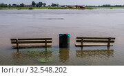 High water on the IJssel with the ferry of Dieren and two benches in the water in The Netherlands. Стоковое фото, фотограф Zoonar.com/D.Kloeg/Commee / easy Fotostock / Фотобанк Лори
