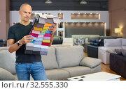 Купить «Portrait of man holding and choosing samples of upholstery fabric in furniture salon», фото № 32555330, снято 29 октября 2018 г. (c) Яков Филимонов / Фотобанк Лори