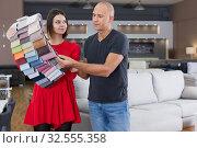 Купить «Consultant helping man choosing upholstery fabric», фото № 32555358, снято 29 октября 2018 г. (c) Яков Филимонов / Фотобанк Лори
