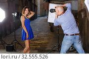 Купить «Professional photo shooting outdoors. Attractive female model posing to photographer on city street», фото № 32555526, снято 5 октября 2018 г. (c) Яков Филимонов / Фотобанк Лори