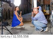 Купить «Professional photo shooting outdoors. Attractive female model posing to photographer on city street», фото № 32555558, снято 5 октября 2018 г. (c) Яков Филимонов / Фотобанк Лори