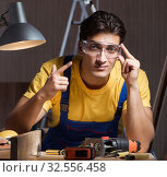 Купить «The worker working in repair workshop in woodworking concept», фото № 32556458, снято 11 августа 2017 г. (c) Elnur / Фотобанк Лори