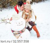 Glückliches Paar im Winter baut zusammen einen Schneemann. Стоковое фото, фотограф Zoonar.com/Robert Kneschke / age Fotostock / Фотобанк Лори