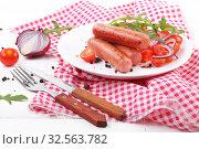 Купить «Fried sausages with tomatoes, onions, arugula and mustard on a white wooden background», фото № 32563782, снято 3 декабря 2019 г. (c) Марина Володько / Фотобанк Лори