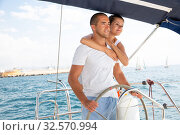 Купить «Couple standing at yacht wheel along coast of Barcelona», фото № 32570994, снято 10 декабря 2019 г. (c) Яков Филимонов / Фотобанк Лори