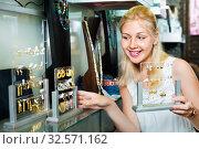 Купить «Portrait of young cheerful woman choosing earrings», фото № 32571162, снято 13 декабря 2019 г. (c) Яков Филимонов / Фотобанк Лори