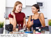Купить «Smiling young girlfriend looking cosmetics before make-up in home interior», фото № 32571202, снято 29 августа 2018 г. (c) Яков Филимонов / Фотобанк Лори
