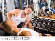 Купить «Young attractive man making biceps curls in gym», фото № 32571226, снято 4 октября 2016 г. (c) Яков Филимонов / Фотобанк Лори